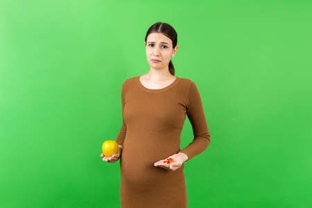 apple and a heap of pills in pregnant woman's hands at colorful background with copy space. Making a choice during pregnancy concept.