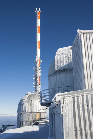 outpost: Sky observatory on the mountain top Wendel-stein Bavaria in wintertime with telecommunication mast against deep blue skies.