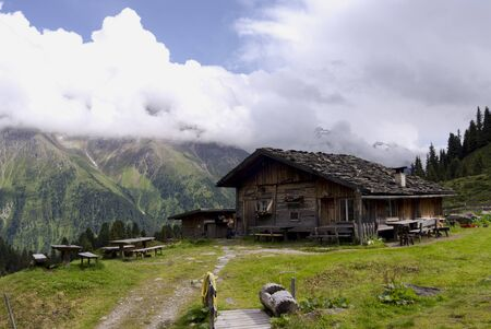 mountain hut: Scenic wood mountain hut in Austrian alps Tirol with mountain range in the back.