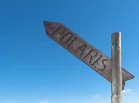 cardinal points: Poste indicador con la escritura de Polaris direcci�n norte contra el cielo azul. Foto de archivo