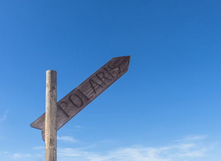 spacial: Signpost with writing Polaris directing north against blue sky.