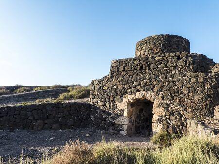shaft: Historic lime shaft kiln on Canary Islands against blue sky.