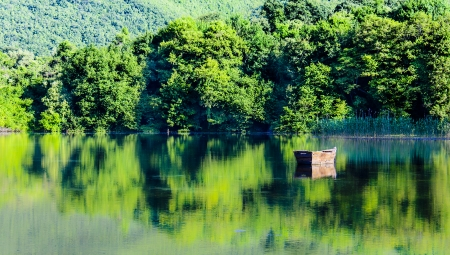 beautiful photo of a lake in SKopje and its reflections of the trees and boat  photo