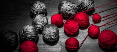 red and grey balls of thread in a beautiful grey