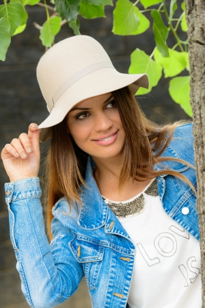 young woman wearing a white hat and smiling  photo