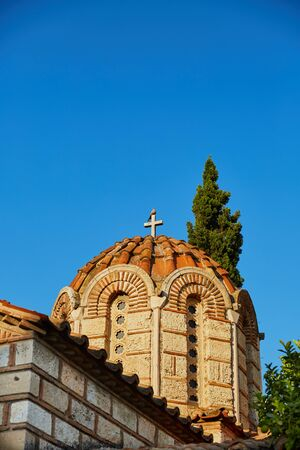 Greek orthodox church domed roof with a dove over the cross at blue sky with green trees