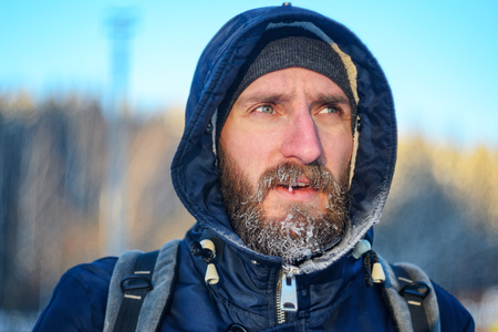 Close up portrait of the young man with frozen icy hairs on head and beard