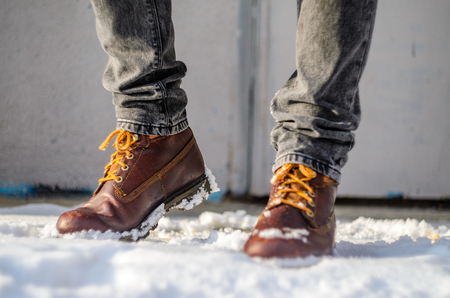 Brown leather shoes in the snow. Legs in the warmth concept Stock Photo