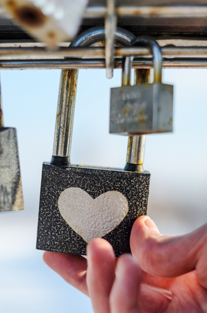 Hand touches padlock with heart pattern. Checking the strength of the concept Stock Photo