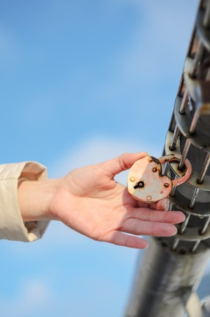 Padlock in the shape of a heart on the palm. Checking the strength of the concept Stock Photo