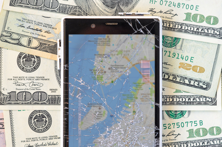 Broken Smartphone with blur map on money banknotes background. Loss of connection and lost in the journey concept