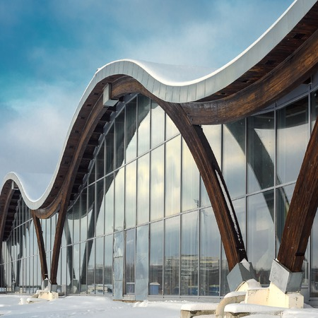 minsk: MINSK, BELARUS - January 15, 2017: Sports complex Olympic reserve. Pool National Olympic Training Center in athletics in Minsk, Belarus. Element of modern building with circular shape facade against blue clear sky. Design of arched roof and stained glass