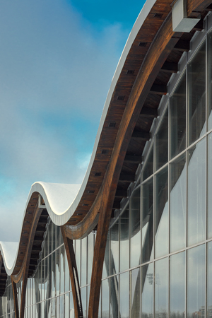 piscina olimpica: MINSK, BELARUS - January 15, 2017: Sports complex Olympic reserve. Pool National Olympic Training Center in athletics in Minsk, Belarus. Element of modern building with circular shape facade against blue sky. Design of arched roof and stained glass system