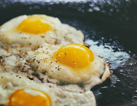 Vintage photo of Fried eggs in a frying pan. Process of cooking eggs closeup. Food Background Stock Photo