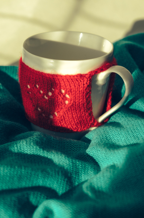 romantic places: Still life of Cozy Mug in red knitted mitten with heart pattern on mint color background. Retro Look