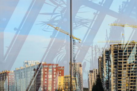 Construction site in the reflection of the glass facade of a modern building. Abstract background Stock Photo