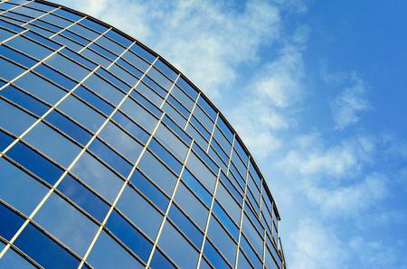 Fachada de vidrio curvado del edificio moderno contra el cielo azul. Vista en perspectiva desde abajo hacia arriba. Fondo abstracto