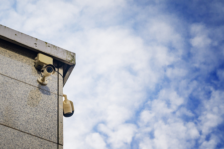 closed circuit television: Two Security cameras on the side of an modern building against blue sky Stock Photo