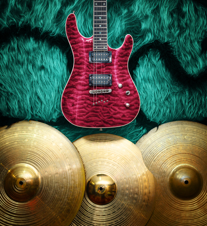 convex shape: Purple electric guitar with three cymbals on turquoise color faux fur wall. Musical instruments background Stock Photo
