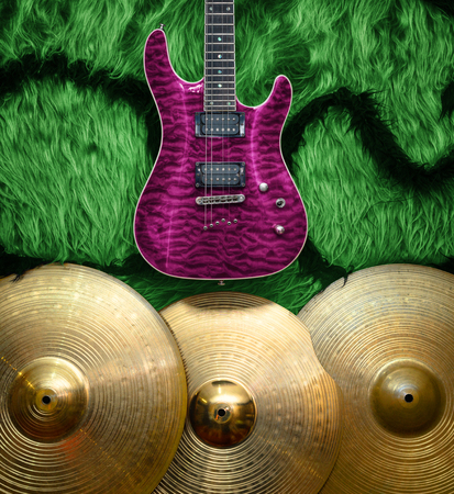 Purple electric guitar with three cymbals on green faux fur wall. Musical instruments background Stock Photo