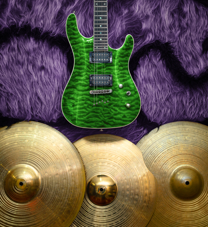 Green electric guitar with three cymbals on faux fur wall. Musical instruments background Stock Photo
