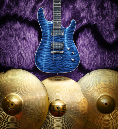 Blue electric guitar with three cymbals on faux fur wall. Musical instruments background Stock Photo