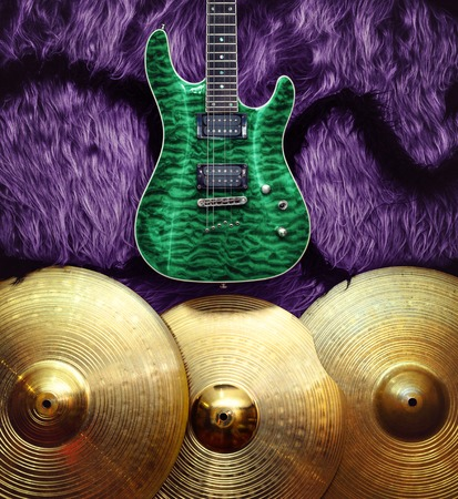 Green electric guitar with three cymbals on purple faux fur wall. Musical instruments background
