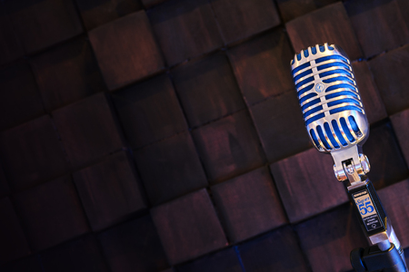 shure: Silver old fashioned stage microphone- SHURE Super 55 Deluxe against wood background. Karaoke, vocal learning, music shop or radio concept. Retro style mic ready to rock