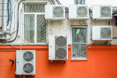 airs: Chaotically located air conditioners on the wall. Element of urban urban landscape. Urban background. Many compressor airs are hanging on a wall