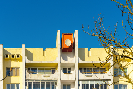 Top part of facade moden building. Detail of hostel building against blue sky background. Ussr architecture