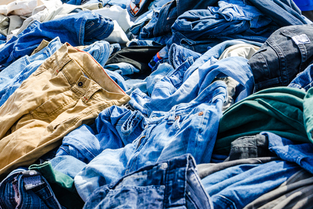Heaps of clothing on the second hand market. Pile of second hand clothes at a garage sales 版權商用圖片