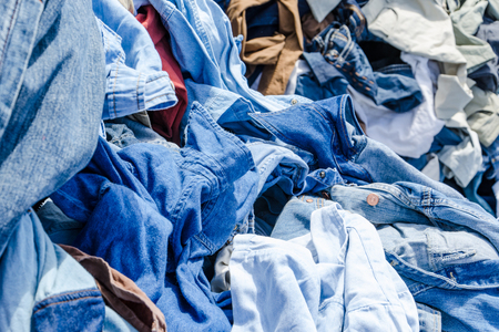 messy clothes: Heaps of clothing on the second hand market. Pile of second hand clothes at a garage sales Stock Photo