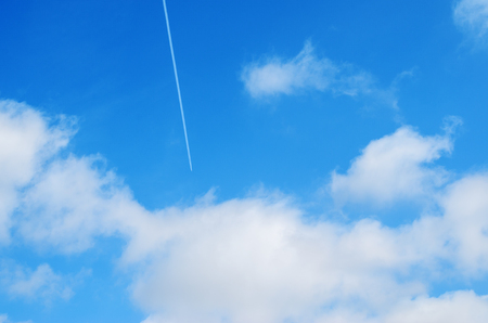 Airplane flies in white clouds in a blue sky and leaving trail Stock Photo