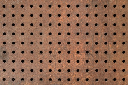 metal grate: Rusty texture of perforated metal. Regular pattern of holes in a sheet of metal. Rusty iron background with holes Stock Photo