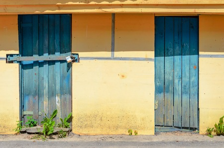 stucco facade: Yellow plastered facade with blue wooden doors. Yellow Wall Background Stock Photo