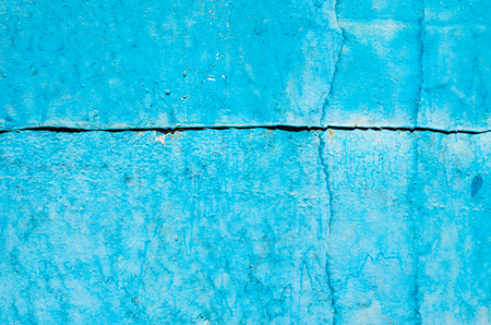 Cracked paint on old metal texture. Blue color. Rusted surface. Joint of steel sheets Stock Photo