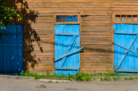 rot: Old blue doors on wooden facade. Wood background
