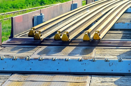 special steel: Railhead elements. Transportation of long new rails on a freight car. Endless path. The rail lash. Special load.