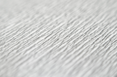 White texture of embossed paper. Macro. Shallow depth of field. Abstract background with deep grooves in the texture of corrugated paper. Pattern of lines on a diagonal Stock Photo
