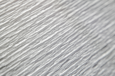 White texture of embossed paper. Macro. Shallow depth of field. Abstract background with deep grooves in the texture of corrugated paper. Pattern of lines on a diagonal Reklamní fotografie