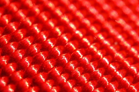 Red nylon belt close-up. Shallow depth of field. The interweaving of the fibers in the belt texture as abstract background Stock Photo
