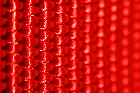 interweaving: Red nylon belt close-up. Shallow depth of field. The interweaving of the fibers in the belt texture as abstract background Stock Photo