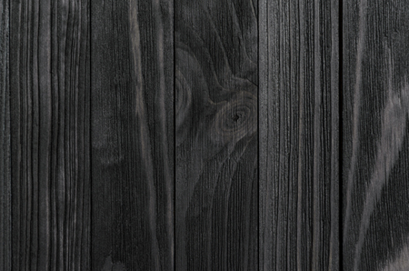 cohesive: Black Wood Texture. Black stained wooden billboard close-up. Vertical direction cohesive boards. Wavy pattern of wood fibers