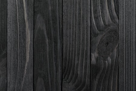 Black Wood Texture. Black stained wooden billboard close-up. Vertical direction cohesive boards. Wavy pattern of wood fibers