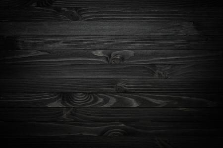 Dunkles schwarzes hölzernes Beschaffenheitshintergrund von oben angesehen. Die Holzbohlen sind horizontal gestapelt