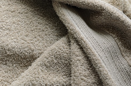 Casually lying towel of beige color. Towel folds background