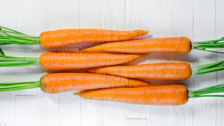 Geometrically laid out fresh carrots on a white wooden table top view. Fresh carrots on white background.
