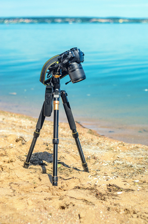 Camera on a tripod near the seaside removes of seashells on the sand. Photographic equipment in the process of shooting the landscape. Camera while taking a photo or time-lapse
