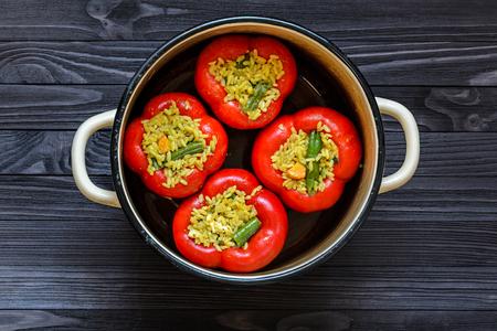 暗い素朴なキッチンで黄色鍋 4 赤ピーマンはテーブル トップ ビューの背景です。調理プロセス 写真素材
