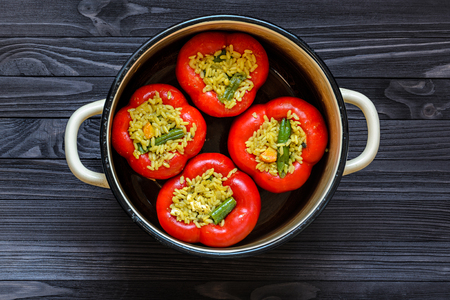 Four red stuffed peppers in a yellow saucepan on dark rustic kitchen table background, top view. Cooking process Imagens